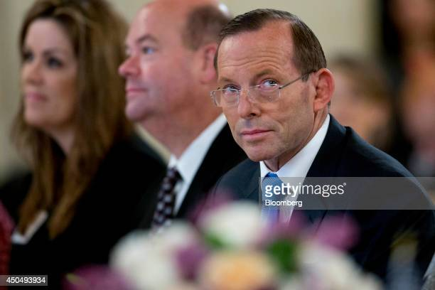 Tony Abbott Australia's prime minister right waits to speak during an event at the US Chamber of Commerce in Washington DC US on Thursday June 12...