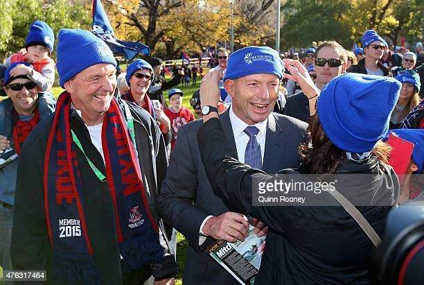 Tony Abbott has his beanie adjusted as he joins Neale Daniher to walk to the MCG ahead of the round 10 AFL match between the Melbourne Demons and the...