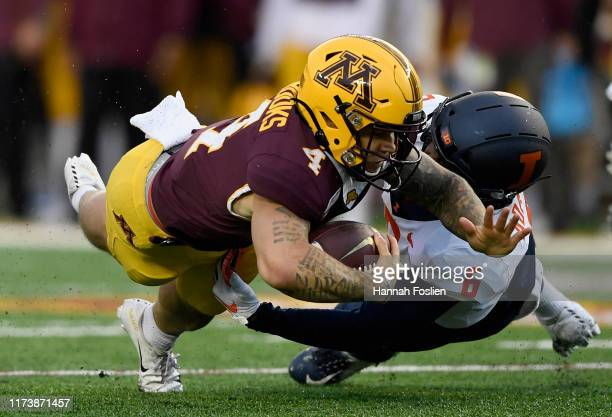 Tony Adams of the Illinois Fighting Illini tackle Shannon Brooks of the Minnesota Gophers during the third quarter of the game at TCF Bank Stadium on...