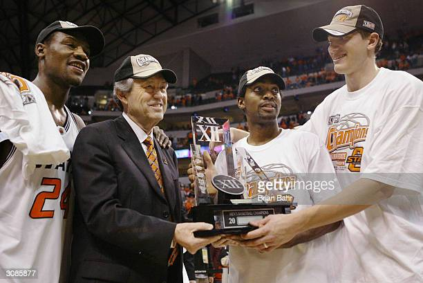 Tony Allen, head coach Eddie Sutton, John Lucas and Stephen Graham of the Oklahoma State Cowboys pose with the Big 12 trophy after being named to the...