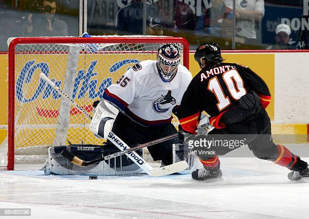 Tony Amonte of the Calgary Flames dekes Alex Auld of the Vancouver Canucks before scoring a shootout goal during their NHL game at General Motors...