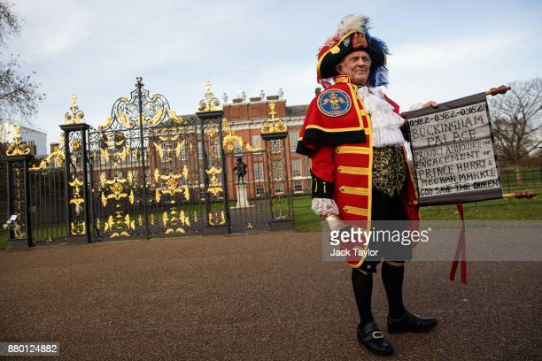 Tony Appleton dressed as a town crier poses with an announcement of Prince Harry and Meghan Markle's engagement outside Kensington Palace in...