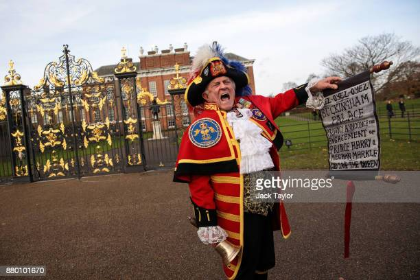 Tony Appleton dressed as a town crier rings a bell as he calls out an announcement of Prince Harry and Meghan Markle's engagement outside Kensington...