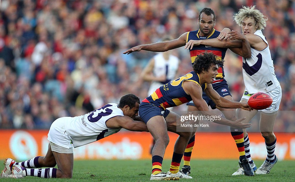 Tony Armstrong of the Crows gets the ball away under pressure from Roger Hayden of the Dockers during the round 11 AFL match between the Adelaide Crows and the Fremantle Dockers at AAMI Stadium on June 5, 2010 in Adelaide, Australia.
