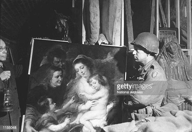 Tony Baea of the U.S. First Army, looks at a Rubens painting, looted by the Nazis and one of many valuable works found in an underground cave in...