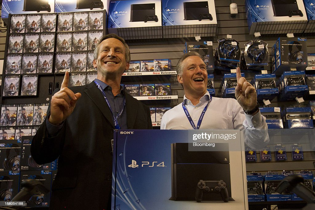 Tony Bartel, president of GameStop Corp., left, and Tim Bender, senior vice president of sales at Sony Computer Entertainment America LLC, pose with the first Sony PlayStation 4 console of the night to be sold during its midnight launch event in San Francisco, California, U.S., on Thursday, Nov. 14, 2013. Sony Corp., poised to release the PlayStation 4 game console this week, is confident it can meet analysts' sales estimates of 3 million units by year-end, exploiting an early advantage over Microsoft Corp.'s Xbox One. Photographer: Erin Lubin/Bloomberg via Getty Images