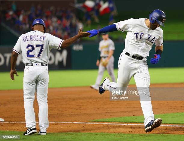 Tony Beasley of the Texas Rangers congratulates Joey Gallo as he runs the bases after hitting his fortieth MLB home run in the second inning against...