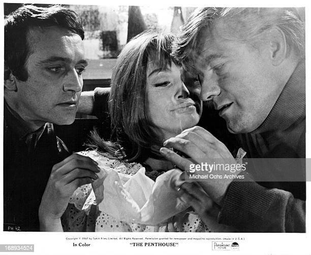 Tony Beckley and Norman Rodway have Suzy Kendall sandwiched between them as they hand feed her party favors in a scene from the film 'The Penthouse'...