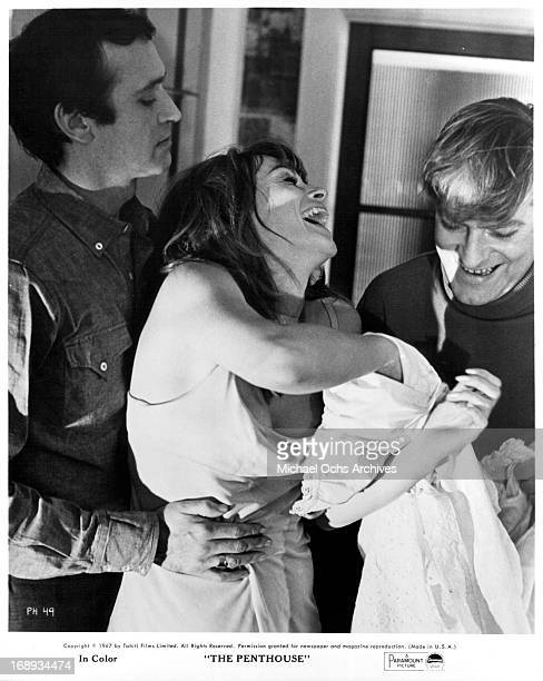 Tony Beckley has his hands around Suzy Kendall waist as Norman Rodway helps her take her clothes off in a scene from the film 'The Penthouse' 1967