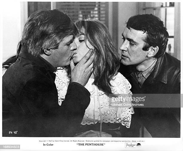 Tony Beckley watches Norman Rodway kiss Suzy Kendall in a scene from the film 'The Penthouse' 1967