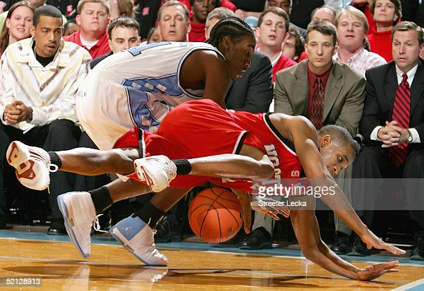 Tony Bethel of the North Carolina State Wolfpack dives for a loose ball with Quentin Thomas of the North Carolina Tar Heels during their game on...