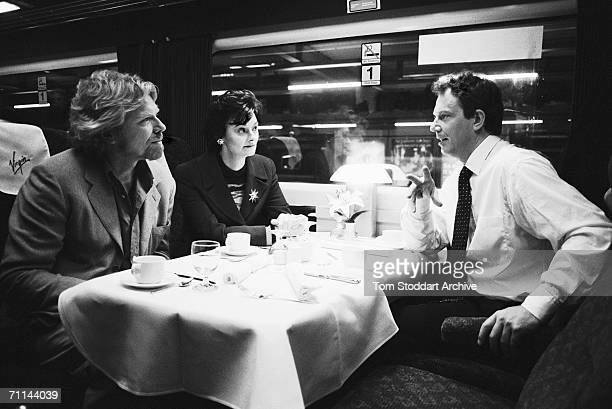 Tony Blair and his wife Cherie on a Virgin train with Sir Richard Branson during Blair's successful 1997 General Election campaign to become...