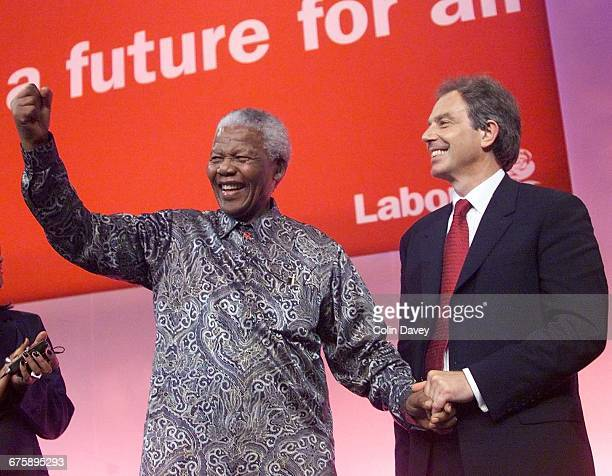 Tony Blair holds Nelson Mandela's hand as he waves to delegates on the last day of the Labour Party Conference Brighton, 28th September 2000.
