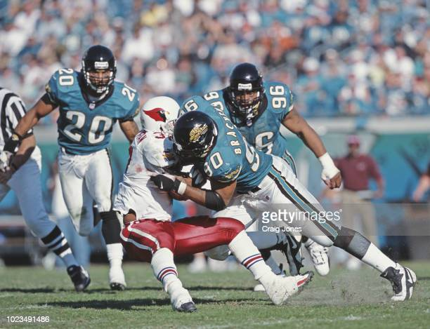Tony Brackens Defensive End for the Jacksonville Jaguars tackles Michael Pittman Running Back of the Arizona Cardinals during their American Football...