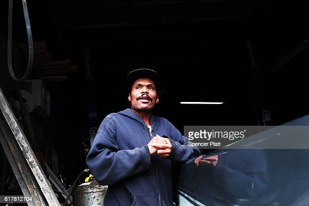 Tony Breher a Hillary Clinton supporter stands in a car garage on October 24 2016 in Youngstown Ohio Ohio has become one of the key battleground...