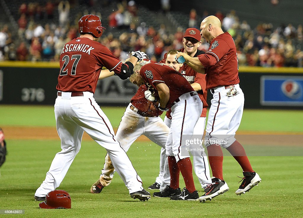 Tony Campana #19 of the Arizona Diamondbacks drives in the winning run against the Milwaukee Brewers in the ninth inning and is congratulated by teammates Cody Ross #7, Roger Kieschnick #27 and Chris Owings #16 at Chase Field on June 18, 2014 in Phoenix, Arizona. Arizona won 4-3.