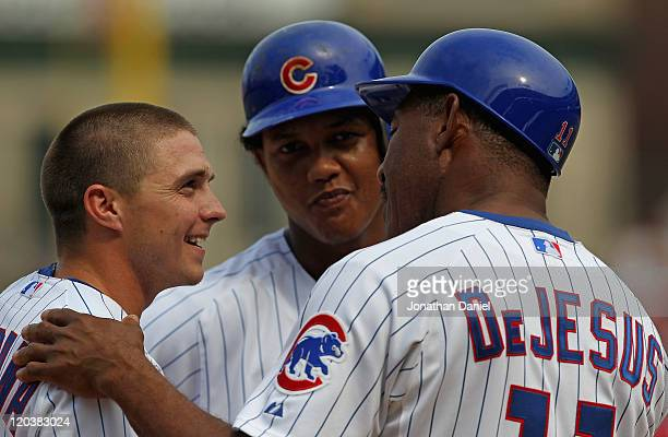 Tony Campana of the Chicago Cubs smiles as he talks to 3rd base coach Ivan DeJesus and Starlin Castro during a Cincinnati Reds pitching change at...