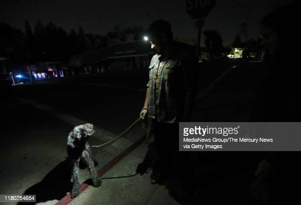 Tony, center, and Lauren Scherba walk their dog Gandalph minutes after the power went out in the Montclair District of Oakland, Calif., on Wednesday,...