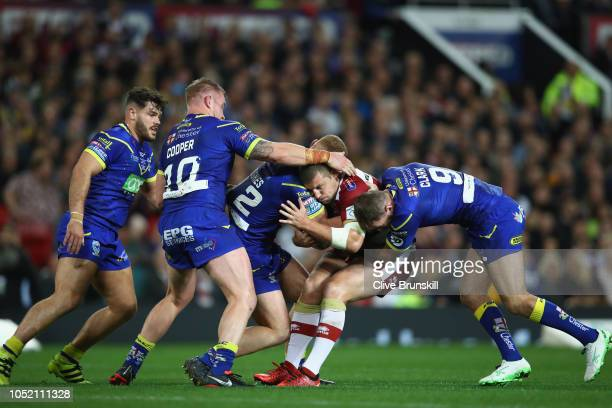 Tony Clubb of Wigan Warriors is held by Jack Hughes and Daryl Clark of the Warrington Wolves during the BetFred Super League Grand Final between...