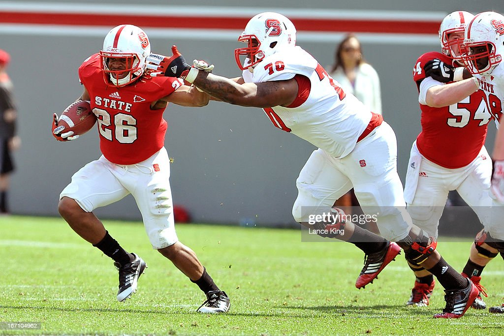 Tony Creecy #26 avoids a tackle by Carlos Gray #70 of the North Carolina State Wolfpack during the Kay Yow Spring Football Game at Carter-Finley Stadium on April 20, 2013 in Raleigh, North Carolina.
