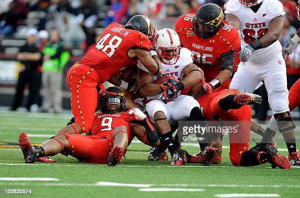 Tony Creecy of the North Carolina State Wolfpack is tackled by Eric Franklin AJ Francis and Demetrius Hartsfield of the Maryland Terrapins at Byrd...