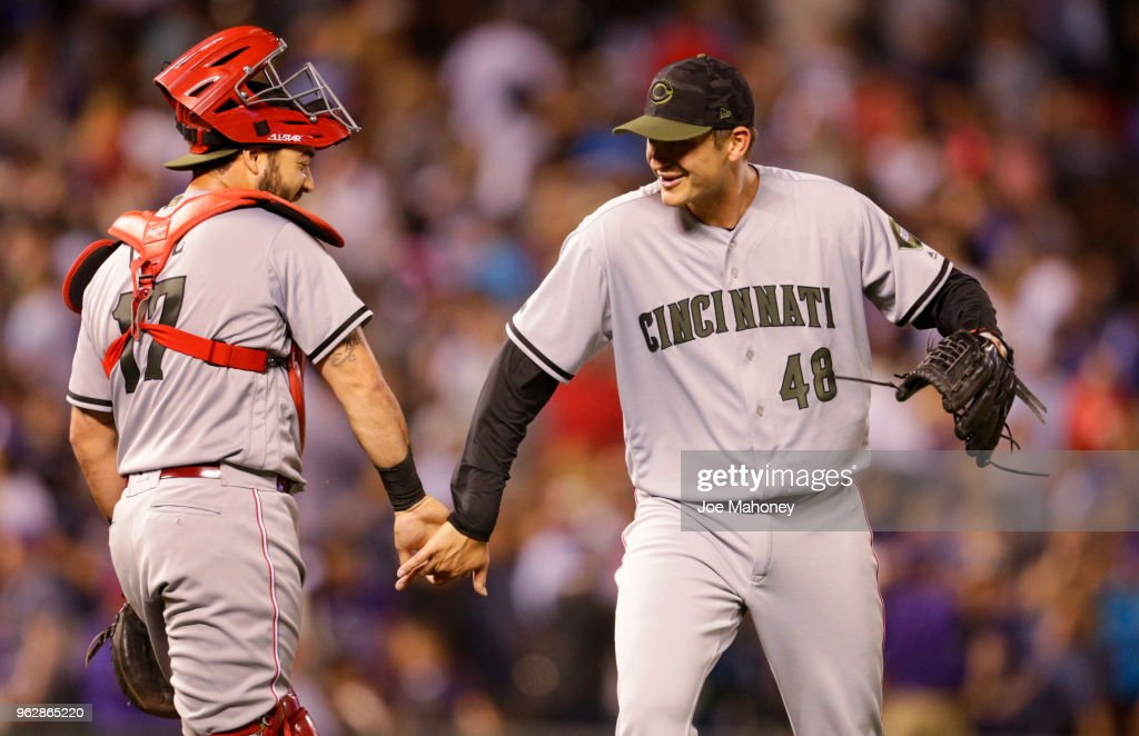 Tony Cruz #17 of the Cincinnati Reds celebrates with Jared Hughes #48 of the Cincinnati Reds after the Reds beat the Colorado Rockies 6-5 at Coors Field on May 26, 2018 in Denver, Colorado. Hughes recorded the save.