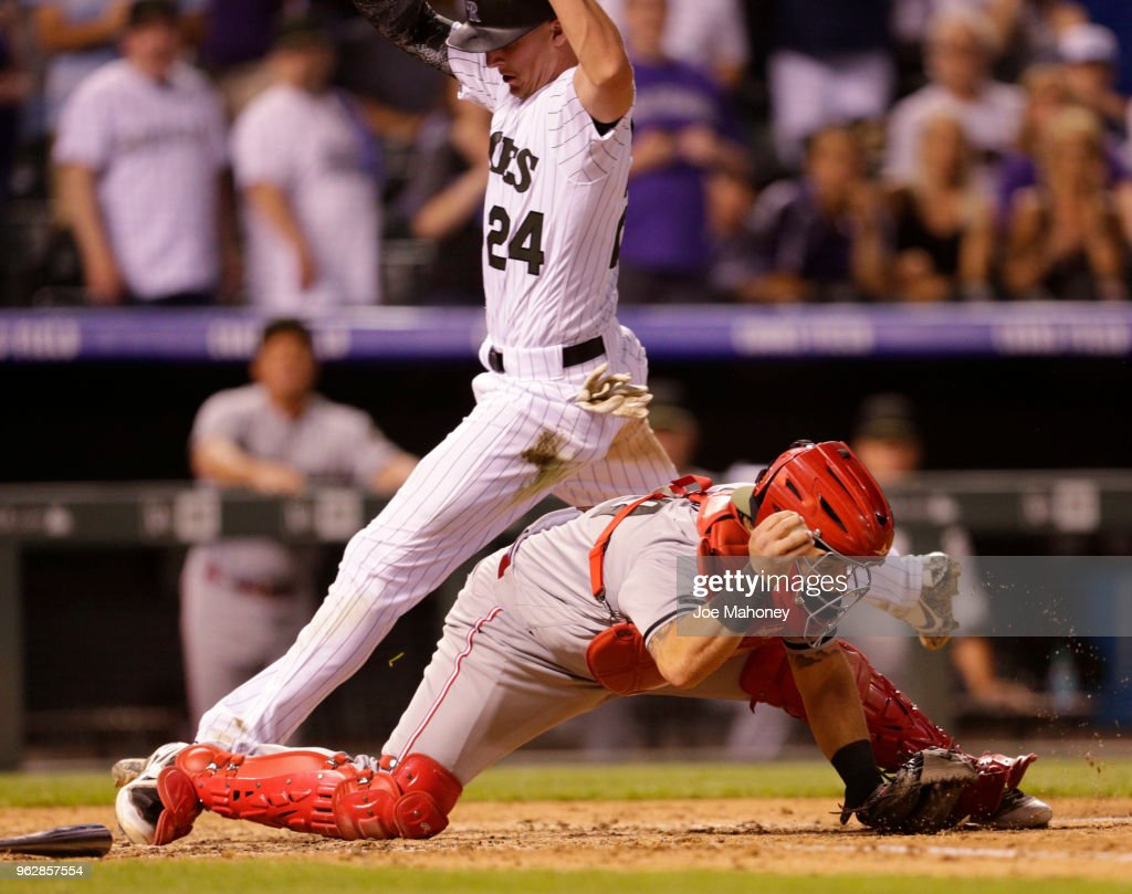 Tony Cruz #7 of the Cincinnati Reds forces out Ryan McMahon #24 of the Colorado Rockies at home in the ninth inning at Coors Field on May 26, 2018 in Denver, Colorado. Cincinnati won 6-5.