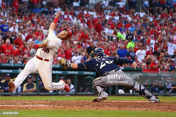 Tony Cruz of the St Louis Cardinals avoids being tagged out by Jonathan Lucroy of the Milwaukee Brewers to score a run in the fourth inning at Busch...