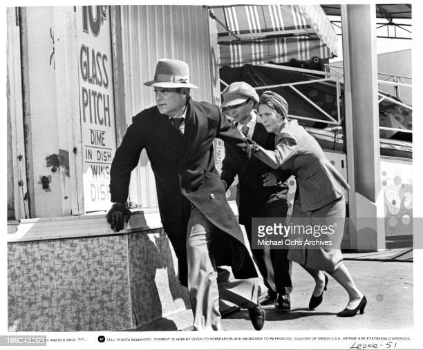 Tony Curtis and Anjanette Comer run for cover in a scene from the film 'Lepke' 1975