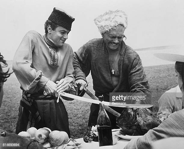 Tony Curtis and Yul Brynner clown around on the set of Taras Bulba in Argentina carving a Thanksgiving turkey with their Cossack sabers while wearing...