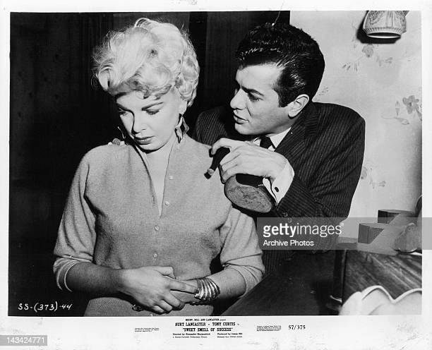 Tony Curtis holds a shoe while leaning over the shoulder of Barbara Nichols in a scene from the film 'Sweet Smell Of Success' 1957