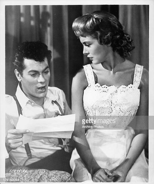Tony Curtis reading piece of paper while Janet Leigh listens in a scene from the film 'Houdini' 1953