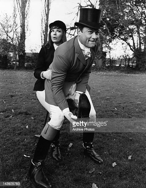 Tony Curtis tries to pull off Fenella Fielding's boot in a scene from the film 'Arrivederci Baby' 1966