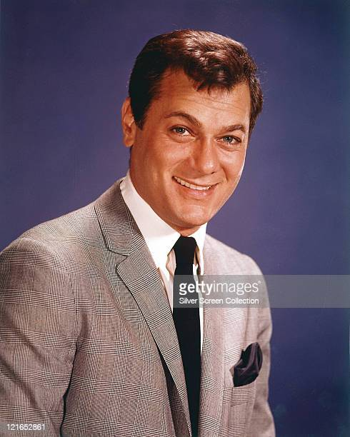 Tony Curtis US actor smiling wearing a grey jacket white shirt and black tie in a studio portrait against a blue background circa 1960