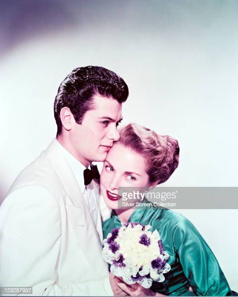 Tony Curtis , US actor, wearing a white dinner jacket with a white shirt and a black bow tie, posing with his wife, Janet Leigh , US actress, who...