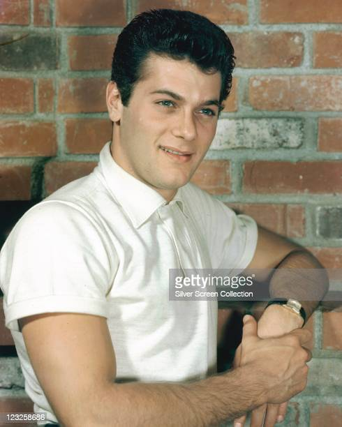 Tony Curtis US actor wearing a white shortsleeved polo shirt posing against a bare brick wall circa 1955