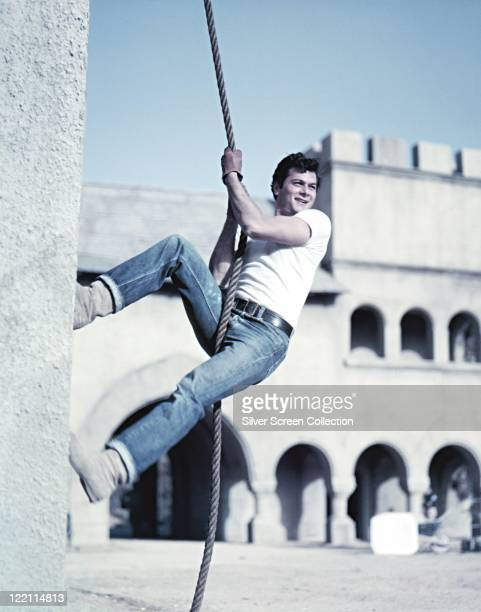 Tony Curtis US actor wearing a white tshirt and blue denim jeans as he climbs the side of a building using a length of rope circa 1955
