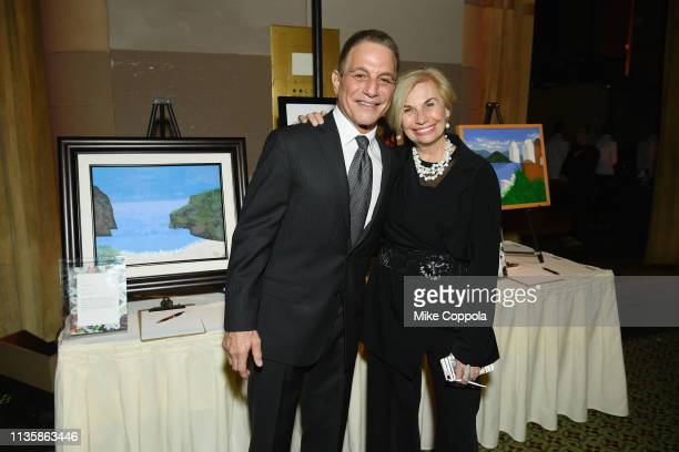 Tony Danza and Karen Bromley pose with art that will be auctioned at the 2019 2nd Annual ADAPT Leadership Awards at Cipriani 42nd Street on March 14...