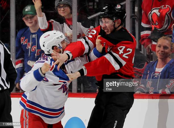 Tony DeAngelo of the New York Rangers and Nathan Bastian of the New Jersey Devils fight in the second period at Prudential Center on April 01 2019 in...