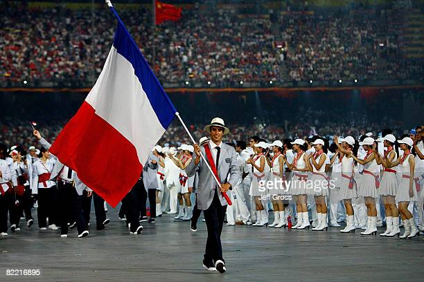 Tony Estanguet of France carries his country's flag during the Opening Ceremony for the 2008 Beijing Summer Olympics at the National Stadium on...