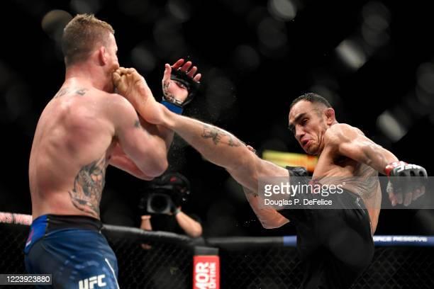 Tony Ferguson of the United States kicks Justin Gaethje of the United States in their Interim lightweight title fight during UFC 249 at VyStar...
