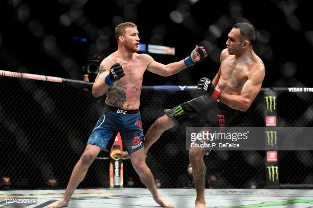 Tony Ferguson of the United States kicks Justin Gaethje of the United States in their Interim lightweight title fight during UFC 249 at VyStar...