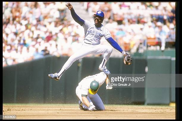 Tony Fernandez of the Toronto Blue Jays leaps over first baseman Mark McGwire of the Oakland Athletics during a game of the 1989 American League...