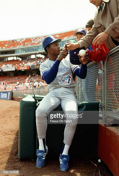Tony Fernandez of the Toronto Blue Jays signs autographs for fans before the start of their Major League Baseball game against the Oakland Athletics...