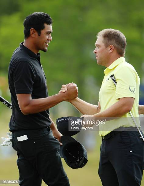 Tony Finau and Daniel Summerhays shake hands after their round on the 18th hole during the third round of the Zurich Classic at TPC Louisiana on...