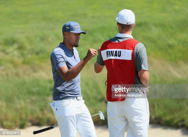 Tony Finau of the United States celebrates with caddie Greg Bodine after making a birdie putt on the 18th green during the third round of the 2018 US...
