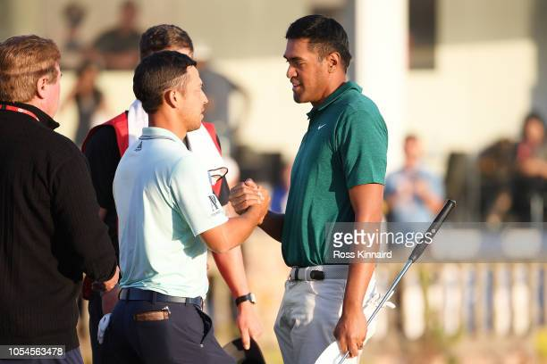 Tony Finau of the United States congratulates Xander Schauffele of the United States on the 18th green after Schauffele won in a playoff during the...