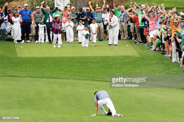 Tony Finau of the United States falls after rolling his ankle while celebrating his holeinone on the seventh hole during the Par 3 Contest prior to...