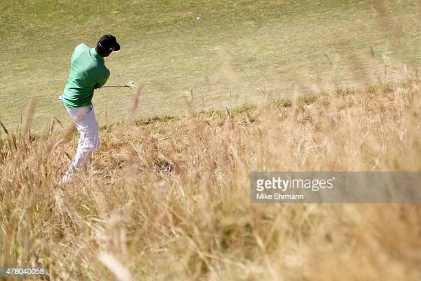 Tony Finau of the United States hits a shot out of the rough on the 12th hole during the final round of the 115th US Open Championship at Chambers...