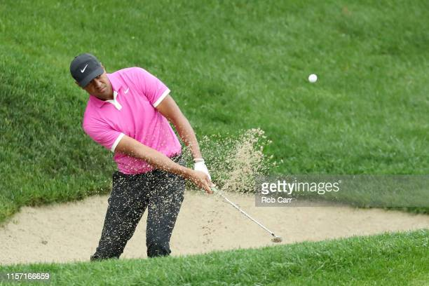 Tony Finau of the United States plays a shot from a bunker on the 15th hole during the first round of the Travelers Championship at TPC River...